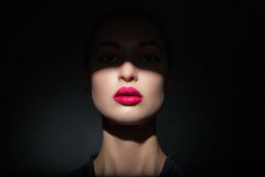 Beautiful model with bright pink lips and face half covered in shadow Stock Photo