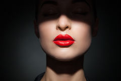 Beautiful model with bright red lips and face half covered in shadow Stock Photo