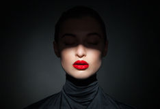 Beautiful model with bright red lips and face half covered in shadow Royalty Free Stock Images