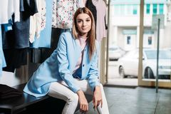 Model brunette girl in stylish clothes, posing in clothing store, a new trend of clothes. Banner for a clothing store. For royalty free stock images