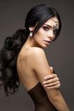 Beautiful model brunette with long curled hair Stock Image