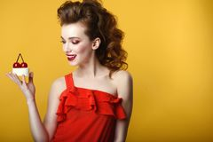 Beautiful model with creative hairstyle and colourful make up holding tasty pastry decorated with cherries on the top Royalty Free Stock Images