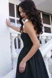 Beautiful model with dark hair wearing elegant black dress Stock Photo