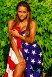 Beautiful model draped in the American Flag. Stock Photo