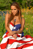 Beautiful Model drapped in the American Flag. Red headed model sitting in a field of flowers drapped in an American flag Royalty Free Stock Photos