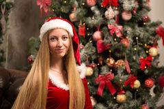 Beautiful model dressed as Santa with near a Christmas tree Stock Images