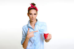 Beautiful model drinks holding red cup and suggesting good taste. Beautiful face model girl like drinking juice with straw wink suggesting good taste soda drink Royalty Free Stock Images