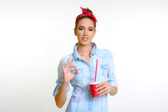 Beautiful model drinks holding red cup and suggesting good taste. Beautiful face model girl like drinking juice with straw wink suggesting good taste soda drink Stock Photos