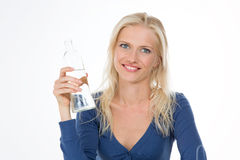 Beautiful model drinks some water from transparent glass bottle. One smiling girl refresh herself Royalty Free Stock Photography