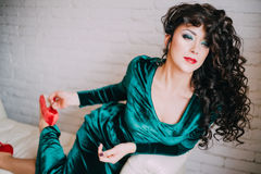 Beautiful model in emerald velvet dress lying on a white couch Royalty Free Stock Images