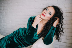 Beautiful model in emerald velvet dress lying on a white couch Royalty Free Stock Photo