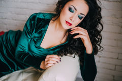 Beautiful model in emerald velvet dress lying on a white couch Stock Photography