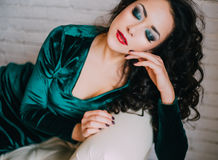 Beautiful model in emerald velvet dress lying on a white couch Stock Photo
