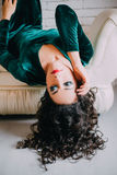 Beautiful model in emerald velvet dress lying on a white couch Stock Photos