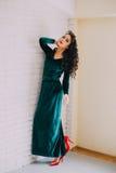 Beautiful model in emerald velvet dress standing near white brick wall Stock Photos