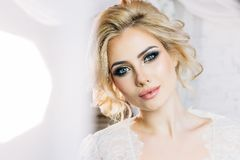 Beautiful model with expressive eyes and beautiful hairdo in whi. Beautiful model with expressive eyes and a sweet smile in a white negligee Royalty Free Stock Photos
