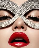 Beautiful Model with Fashion Lips Makeup wearing bright brilliant mask. Masquerade style woman. Holiday celebration look Stock Photography