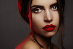 Beautiful model with fashion make-up. Portrait sexy woman with glamour red lips makeup, strong eyeshadows, hairstyle Royalty Free Stock Photo