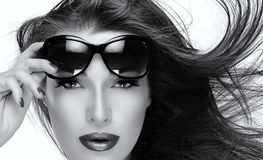 Beautiful Model in Fashion Sunglasses. Monochrome Closeup Portrait. Beautiful fashion model girl with healthy long hair in motion holding her shades on forehead royalty free stock photography