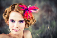 Beautiful model with feather in hair. Beautiful caucasian model with red curly hair pinned up with a feathered flower sitting in the tall grass Royalty Free Stock Photos