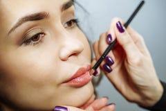 Beautiful model girl applying lipgloss. Lipstick. Professional Make-up royalty free stock photography