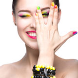 Beautiful model girl with bright colored makeup and nail polish in the summer image. Beauty face. Short colored nails.