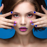 Beautiful model girl with bright makeup and colored  nail polish. Beauty face. Short colorful nails. Picture taken in the studio on a blue background Stock Photos