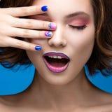 Beautiful model girl with bright makeup and colored  nail polish. Beauty face. Short colorful nails Royalty Free Stock Photos