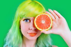 Beautiful model girl with colorful hairstyle takes red juice on green background Royalty Free Stock Photography