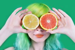 Beautiful model girl with colorful hairstyle takes red and yellow juice on green background Royalty Free Stock Image