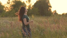Beautiful model girl dressed in jeans and a green shirt on the field in sunlight. Stroking her long hair and looking at stock video footage