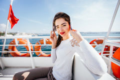 Beautiful model girl hiding from the bright sun newspaper sitting on a boat cruise Trips tourist Stock Photography