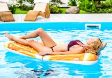 Beautiful model girl lies on shapes air mat. In swimming pool royalty free stock photography