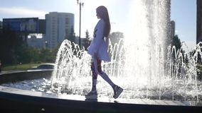 A beautiful model girl walking along the edge of a fountain with beautiful highlights. HD, 1920x1080. slow motion. A beautiful model girl walking along the edge stock video footage
