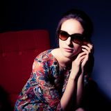 Beautiful model in glasses on a chair Royalty Free Stock Image