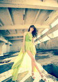 Beautiful model in green dress posing in grunge location Royalty Free Stock Image
