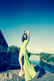 Beautiful model in green dress posing in grunge location Royalty Free Stock Photos