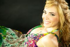 Beautiful model with happy smile. And coloured dress looking into camera Stock Images