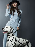 Beautiful model in a hat with beautiful makeup and a dalmatian dog. Studio photoshoot Royalty Free Stock Photos