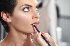 Beautiful model having lip liner applied by makeup artist Royalty Free Stock Photo