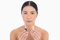 Beautiful model holding lip gloss Stock Image