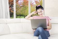 Beautiful model with laptop smiling on sofa Stock Photography