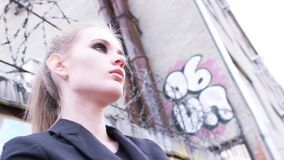 Beautiful model with light brown hair, brown eyes and perfect stylish makeup standing near the wall with razor wire in a. Black jacket. Modern urban style stock video