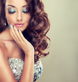Beautiful model with long curly hair. Fashion makeup and silver nails stock photo