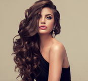 Beautiful model with long, dense and curly hairstyle.