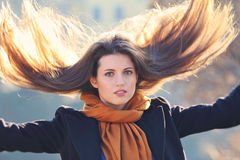 Beautiful model with long hair in motion. Beautiful model with long hairs in motion against sun light Stock Image