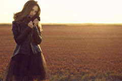 Beautiful model with long hair wearing black veiling dress and stylish leather jacket standing in the deserted field at sunset. Young beautiful glam model with Stock Photo
