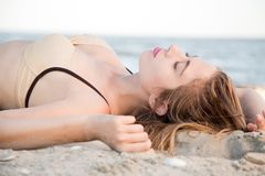 Beautiful model lying in sand Stock Photography