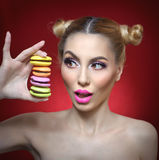 Beautiful model with makeup and creative hairstyle holding colorful macaroons, studio shoot on red background. Diet, dieting concept. Sweets. woman with pink royalty free stock photography