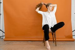 Beautiful model on orange background sitting on the chair in white shirt and black trousers. Touch hair stock photo